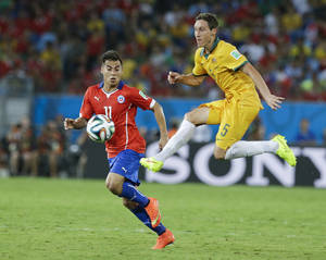 Photo - Australia's Mark Milligan (5) kicks the ball past Chile's Eduardo Vargas (11) during the second half of the group B World Cup soccer match between Chile and Australia in the Arena Pantanal in Cuiaba, Brazil, Friday, June 13, 2014. (AP Photo/Thanassis Stavrakis)