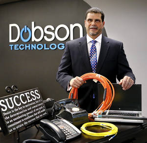 Photo -      Frank Franzese, president of IT, Transport and Telecom Solutions for Dobson Technologies, stands amid a display of telecommunications devices — including an antique crank-generated analog phone next to the latest digital one. He's holding patch cables, which are used for data transmission. Photo by Jim Beckel, The Oklahoman  <strong>Jim Beckel -   </strong>