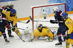 Photo - The puck gets past goalkeeper Valentina Wallner of Sweden for a third goal by the USA during the first period of the 2014 Winter Olympics women's semifinal ice hockey game at Shayba Arena Monday, Feb. 17, 2014, in Sochi, Russia. (AP Photo/Julio Cortez)