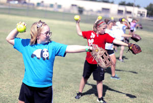 Photo - Maggie Brown, left, practices throwing with other girls in a drill during a softball camp Monday at the Whittier Recreation Center in Norman. PHOTOs BY GARETT FISBECK, THE OKLAHOMAN