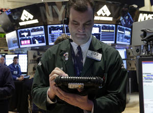 photo - Trader William Lawrence works Friday on the floor of the New York Stock Exchange. AP Photo