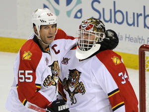 Photo - Florida Panthers' Ed Jovanovski (55) celebrates with goaltender Tim Thomas (34) after defeating the Buffalo Sabres during an NHL hockey game in Buffalo, N.Y., Tuesday, Jan. 21, 2014.  Florida won 4-3. (AP Photo/Gary Wiepert)