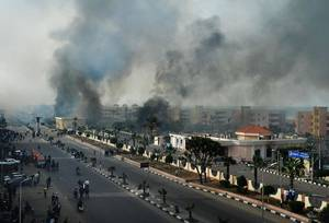 photo - Smoke rises after Egyptian protesters clash with police, unseen, in Port Said, Egypt, Sunday, Jan. 27, 2013.  Violence erupted briefly when some in the crowd fired guns and police responded with volleys of tear gas, witnesses said. State television reported 110 were injured. Egyptian health officials say 3 have been killed in clashes between protesters and police in Port Said. (AP Photo)