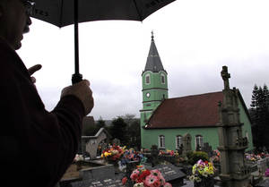 Photo - Government worker Ademir Rost points out a Lutheran church inside a cemetery where German-Brazilians are buried, during a tour of German-Brazilian areas of interest in the southern province of Rio do Grande do Sul, Brazil, Friday, June 28, 2014. German-Brazilians in the region are supporting Germany and Brazil at the World Cup soccer tournament, but if and when the two sides meet, they say they'll support Brazil. (AP Photo/Chris Brummitt)