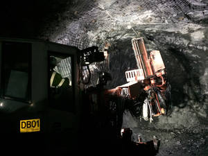 Photo - In this May, 2014 photo provided by Eagle Mine a rock bolter, which drills and installs bolts to stabilize the mine, moves through a tunnel at  the mine in Marquette County, Mich. The nickel and copper operation, scheduled to begin production this fall, will pump $4 billion into Marquette County over its eight-year lifespan and employ about 300 while generating economic activity that will create 1,200 additional jobs, according to the company. (AP Photo/Courtesy Eagle Mine)
