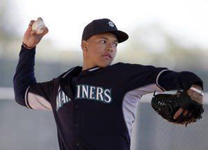 Photo - Seattle Mariners pitcher Taijuan Walker throws in a bullpen session during spring training baseball practice, Thursday Feb. 20, 2014, in Peoria, Ariz. (AP Photo/Tony Gutierrez)