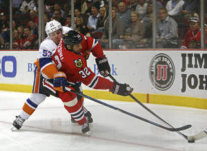 Photo - New York Islanders' Casey Cizikas tries to poke the puck away from Chicago Blackhawks' Michal Rosival during the first period of an NHL hockey game in Chicago on Friday, Oct. 11, 2013. (AP Photo/Charles Cherney)
