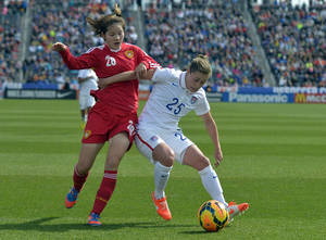 Photo - China midfielder Zhang Xin (28) and USA defender Megan Klingenberg (25) fight for the ball during the first half of an international friendly soccer match  in Commerce City, Colo., on Sunday, April 6, 2014. (AP Photo/Jack Dempsey)
