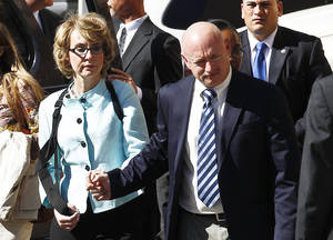 Photo - FILE - In a Thursday, Nov. 8, 2012 file photo, former Democratic Rep. Gabrielle Giffords, left, and her husband Mark Kelly holds her hand as they leave after the sentencing of Jared Loughner, in back of U.S. District Court, in Tucson, Ariz. Giffords and her husband launched a political action committee aimed at curbing gun violence on Tuesday, Jan. 8, 2013, as her Arizona hometown paused to mark the second anniversary of a deadly shooting rampage that left her with severe injuries.  (AP Photo/Ross D. Franklin, File)