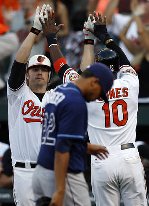 photo -   Baltimore Orioles' Mark Reynolds, left, and Adam Jones (10) celebrate after Jones scored on a single by teammate Manny Machado as Tampa Bay Rays pitcher Chris Archer, front, walks off the field after a baseball game in Baltimore, Thursday, Sept. 13, 2012. Baltimore won 3-2 in 14 innings. (AP Photo/Patrick Semansky)