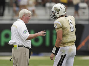Photo - Central Florida head coach George O'Leary, left, talks with quarterback Blake Bortles (5) during a timeout in the first half of an NCAA college football game against South Carolina  in Orlando, Fla., Saturday, Sept. 28, 2013.(AP Photo/John Raoux)