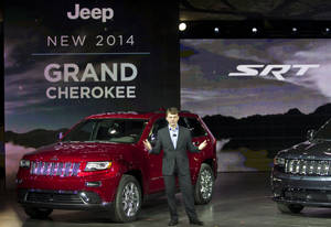 photo - Mike Manley, President and CEO of Jeep, unveils the 2014 Jeep Grand Cherokee, at the North American International Auto Show, Monday, Jan. 14, 2013, in Detroit, Mich. (AP Photo/Tony Ding)