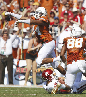 Photo - Texas' Jackson Jeffcoat, left, celebrates after bringing down OU's Blake Bell during Saturday's game in Dallas. Bell completed only 12 of 26 passes as Texas won 36-20. Photo by Bryan Terry, The Oklahoman