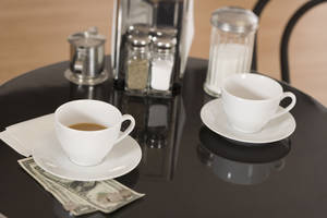 Photo - Money and cups on restaurant table