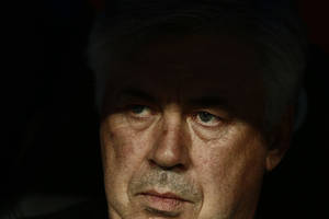 Photo - Real Madrid's coach Carlo Ancelotti from Italy sits on the bench during a Spanish La Liga soccer match between Real Madrid and Valencia at the Santiago Bernabeu stadium in Madrid, Spain, Sunday May 4, 2014. (AP Photo/Daniel Ochoa de Olza)