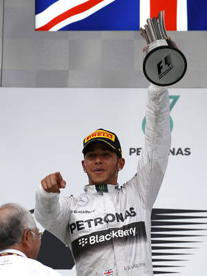 Photo - Mercedes driver Lewis Hamilton of Britain gestures as he holds his trophy aloft after winning the Malaysian Formula One Grand Prix at Sepang International Circuit in Sepang, Malaysia, Sunday, March 30, 2014. (AP Photo/Vincent Thian)