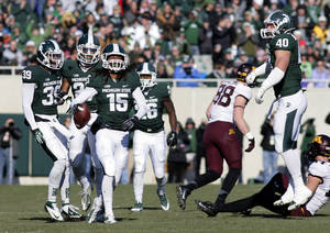 Photo - Michigan State players, including Jermaine Edmondson (39), Kurtis Drummond, Trae Waynes (15), R.J. Williamson (26) and Max Bullough (40), celebrate Waynes' interception against Minnesota during the second quarter of an NCAA college football game, Saturday, Nov. 30, 2013, in East Lansing, Mich. (AP Photo/Al Goldis)
