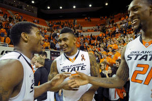 photo - Oklahoma State guard Marcus Smart, left, celebrates with guard Le'Bryan Nash, center, and forward Kamari Murphy, right following an NCAA college basketball game against Baylor in Stillwater, Okla., Wednesday, Feb. 6, 2013. Oklahoma State won 69-67. (AP Photo/Brody Schmidt)