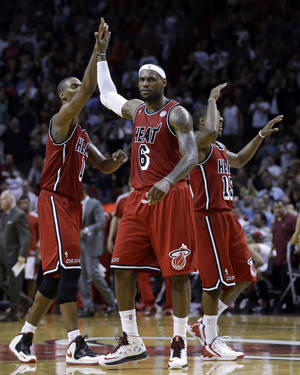 photo - Miami Heat's LeBron James (6) high-fives teammate Chris Bosh (1) after scoring against the Portland Trail Blazers during the second half of an NBA basketball game in Miami, Tuesday, Feb. 12, 2013. The Heat won 117-104.  (AP Photo/Alan Diaz)