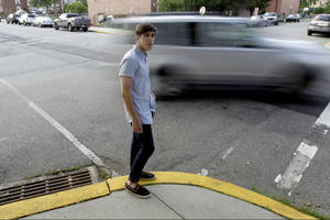photo -   Dylan Young, 18, poses for The Associated Press as a vehicle cruises by, Wednesday, June 6, 2012, in North Arlington, N.J. Young, a senior at North Arlington High, was in a fender-bender accident caused by being distracted while texting and driving. More than half of high school seniors say they text or email while driving, according to a jarring new study that offers the first federal statistics on how common the dangerous habit is in teens. The Centers for Disease Control and Prevention released the numbers Thursday, June 7, 2012. They come from a 2011 survey of about 15,000 high school students across the country. The study found 58 percent of high school seniors said that, in the previous month, they had texted or emailed while driving. (AP Photo/Julio Cortez)