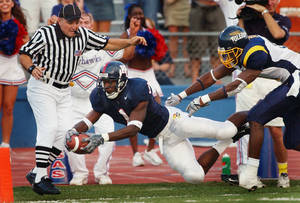 Photo - Kansas running back John Randle (1) dives for a touchdown past Toledo free safety Patrick Body (11) during the first quarter in Lawrence, Kan., Saturday, Sept. 11, 2004. Side judge Jeff Ulery, left, is in position for the call. Randle took an Adam Barmann pass 55 yards for the score. (AP Photo/Orlin Wagner) <strong>ORLIN WAGNER - ASSOCIATED PRESS</strong>