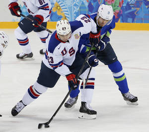Photo - USA forward Dustin Brown takes control of the puck away from Slovenia defenseman Ziga Pavlin during the 2014 Winter Olympics men's ice hockey game at Shayba Arena Sunday, Feb. 16, 2014, in Sochi, Russia. (AP Photo/Petr David Josek)