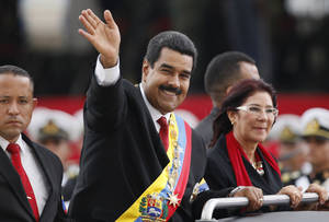 Photo - Venezuela's President Nicolas Maduro waves from a vehicle, next to his companion Cilia Flores, during a military ceremony recognizing him as Commander-in-chief to the military at the Paseo Los  Proceres in Caracas, Venezuela, Friday, April, 19, 2013. Maduro, who has the support of the Chavista bases, needs all the momentum he can muster to consolidate control of a country struggling with shortages of food and medicines; chronic power outages; one of the world's highest homicide and kidnapping rates. (AP Photo/Ariana Cubillos)