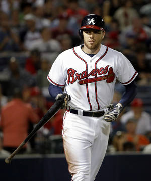 Photo - FILE - In this Sept. 26, 2013, file photo, Atlanta Braves' Freddie Freeman heads to first base after drawing a walk in the second inning of a baseball game against the Philadelphia Phillies in Atlanta. A person familiar with the talks says the Atlanta Braves have reached an agreement on an eight-year deal with Freeman that will be worth about $125 million. The person confirmed the agreement to The Associated Press on condition of anonymity on Tuesday, Feb. 4, 2014, because the Braves haven't announced the deal, which is subject to a successful physical. (AP Photo/David Goldman, File)