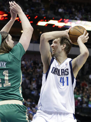 Photo - Dallas Mavericks forward Dirk Nowitzki (41) of Germany looks to pass against Boston Celtics center Kelly Olynyk (41) during the first half an NBA basketball game Monday, March 17, 2014, in Dallas. (AP Photo/LM Otero)