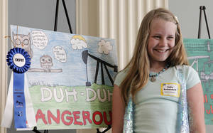 Photo - Moore sixth-grader Katie Buckendorff poses for a photo Tuesday at the state Capitol with her well site safety poster, which earned first place in an Oklahoma Energy Resources Board contest. Photos by David McDaniel, The Oklahoman