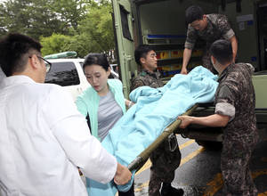 Photo - A wounded South Korean soldier who killed five comrades in a shooting incident on a stretcher is carried from an ambulance upon arrival at a hospital in Gangneung, South Korea, Monday, June 23, 2014. The South Korean army captured the soldier Monday who it says killed five comrades and then fled into the forest where he holed up with a rifle for two days before shooting himself as pursuers closed in. The massive manhunt ended when the 22-year-old sergeant, surnamed Yim, shot himself in the upper left chest as his father and brother approached, pleading with him to surrender, a Defense Ministry official said. (AP Photo/Yonhap, Lee Sang-hack)  KOREA OUT