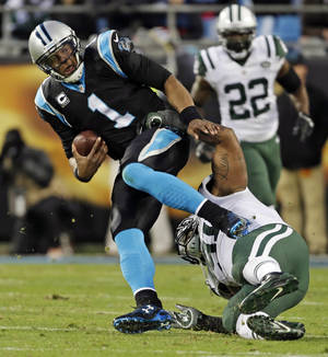 Photo - Carolina Panthers' Cam Newton (1) is tackled by New York Jets' Sheldon Richardson during the first half of an NFL football game in Charlotte, N.C., Sunday, Dec. 15, 2013. (AP Photo/Bob Leverone)