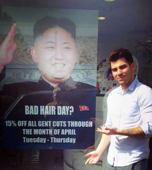 """Photo - This undated photo provided by M&M Hair Academy in South Ealing, west London, shows barber Karim Nabbach standing next to a poster poking fun at North Korean leader Kim Jong-un unusual hairstyle. North Korean diplomats have asked the British government take action against a London hair salon's poster poking fun at distinctively coiffured leader Kim Jong Un. The Foreign Office said Wednesday it had received a letter from the country's embassy objecting to the poster, and was considering its response. The Evening Standard newspaper reported that the letter urged Britain to take """"necessary action to stop the provocation."""" Staff at M&M Hair Academy say they were visited by diplomats from the nearby embassy after putting up a poster featuring a picture of Kim - who sports a distinctive undercut - and the slogan """"Bad Hair Day?"""" Police say they spoke to both parties and determined no crime had been committed. The embassy didn't immediately respond to a request for comment. (AP Photo/M&M Hair Academy)"""