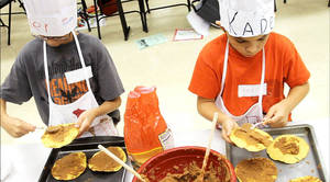 Photo - Kyler Stanley, left, and Kaden Truillo participate in the Kids in the Kitchen cooking school. Photo by Todd Greenlee, for The Oklahoman