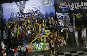Photo - Sprint Cup Series driver Kyle Busch (18) celebrates in victory lane following the NASCAR Sprint Cup Series auto race at Atlanta Motor Speedway in Hampton, Ga., Sunday, Sept. 1, 2013. (AP Photo/John Bazemore)