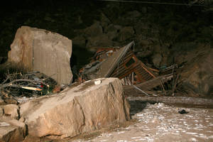 Photo - Flood lights from fire engines parked on nearby state Route 9 shine on the rubble of a two-story log home that was crushed by boulders that broke loose from the cliff above it and killed two people inside the home Thursday, Dec. 12, 2013 in Rockville, Utah. (AP Photo/The Spectrum & Daily News,  Jud Burkett)