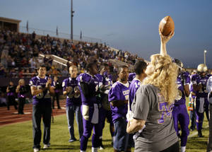 Photo - Kody Turner's mom, Crystal Coleman, show the crowd the game ball before Chickasha's home game against Capitol Hill on Friday. PHOTO BY SARAH PHIPPS, THE OKLAHOMAN