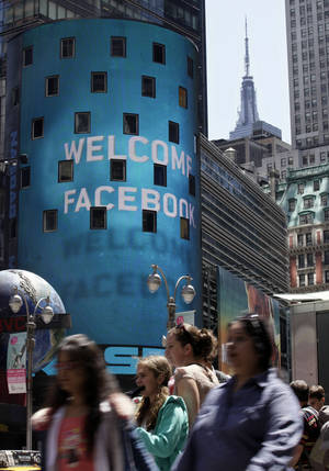 Photo - The top of the Empire State Building, top right, is visible behind the animated facade of the Nasdaq MarketSite, welcoming the Facebook IPO, on May 18 in New York's Times Square. AP Photo