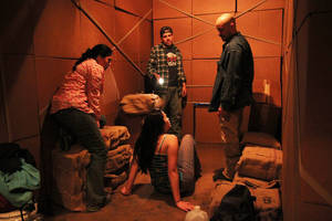 "Photo - This theater publicity image released by DDPR Public Relations shows cast members during a performance of ""LaRuta.""  The off-Broadway company Working Theater is presenting a play about immigrants sneaking across the border is being staged inside a 48-foot-long cargo container. (AP Photo/DDPR Public Relations, Lia Chang)"