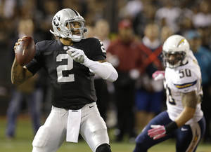 Photo - Oakland Raiders quarterback Terrelle Pryor (2) passes as San Diego Chargers inside linebacker Manti Te'o (50) applies pressure during the first quarter of an NFL football game in Oakland, Calif., Sunday, Oct. 6, 2013. (AP Photo/Ben Margot)