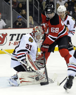 Photo - Chicago Blackhawks goaltender Antti Raanta, left, deflects the puck as New Jersey Devils' Jaraomit Jagr, of the Czech Republic, takes a shot during the second period of an NHL hockey game, Friday, Jan. 3, 2014, in Newark, N.J.  (AP Photo/Bill Kostroun)