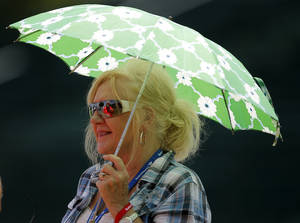 Photo - Gayle Yowell gets shade under her umbrella during the U.S. Senior Open at Oak Tree National in Edmond, Okla., Tuesday, July 8, 2014. Photo by Bryan Terry, The Oklahoman