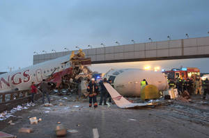 Photo - Rescuers work at the site where a plane careered off the runwaw at Vnukovo Airport in Moscow, Saturday, Dec. 29, 2012. A Tu-204 aircraft belonging to Russian airline Red Wings careered off the runway at Russia's third-busiest airport on Saturday, broke into pieces and caught fire, killing several people. (AP Photo/Alexander Usoltsev)