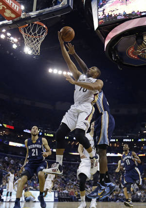 Photo - New Orleans Pelicans shooting guard Eric Gordon (10) goes to the basket in front of Memphis Grizzlies forward Zach Randolph in the first half of an NBA basketball game in New Orleans, Friday, Dec. 13, 2013. (AP Photo/Gerald Herbert)