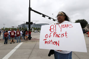 "Photo - FILE - In this Oct. 13, 2014 file photo, Juan Mancias, of Floresville, Texas, a member of the American Indian Movement of Central Texas, holds a sign as he joins others in protest before an NFL football game between the Washington Redskins and Dallas Cowboys in Arlington, Texas. The U.S. Patent Office ruled Wednesday, June 18, 2014, that the Washington Redskins nickname is ""disparaging of Native Americans"" and that the team's federal trademarks for the name must be canceled. (AP Photo/Sharon Ellman, File)"
