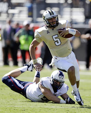 Photo - Central Florida quarterback Blake Bortles (5) runs past Connecticut defensive end Tim Willman, left, for a 16-yard gain during the first half of an NCAA college football game in Orlando, Fla., Saturday, Oct. 26, 2013.(AP Photo/John Raoux)