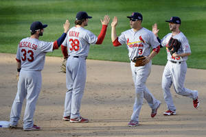 Photo -   St. Louis Cardinals', from left, Daniel Descalso, Pete Kozma, Carlos Beltran and Shane Robinson high-five after Game 3 of the National League division baseball series against the Washington Nationals on Wednesday, Oct. 10, 2012, in Washington. St. Louis won 8-0. (AP Photo/Nick Wass)