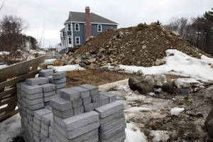 Photo - In this Friday, March 21, 2014, photo,  a single family housing construction is underway in North Andover, Mass. The Commerce Department reports on U.S. construction spending in February on Tuesday, April 1, 2014. (AP Photo/Elise Amendola)