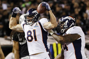 photo - Denver Broncos tight end Joel Dreessen (81) reacts after scoring a touchdown on a 6-yard pass from quarterback Peyton Manning during the first quarter of an NFL football game against the Oakland Raiders in Oakland, Calif., Thursday, Dec. 6, 2012. At right is Broncos tackle Orlando Franklin. (AP Photo/Marcio Jose Sanchez)