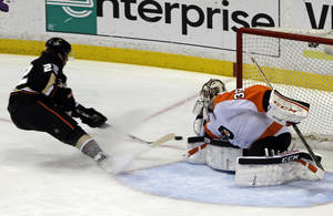 Photo - Anaheim Ducks center Mathieu Perreault (22) gets an assist on this goal by Patrick Maroon, not shown, against Philadelphia Flyers goalie Steve Mason (35) during the first period of an NHL hockey game in Anaheim, Calif., Thursday, Jan. 30, 2014. (AP Photo)